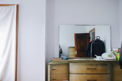 room with mirror on dresser, white sheet up with doorway
