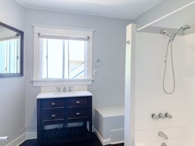 clean white restroom with shower in the tub