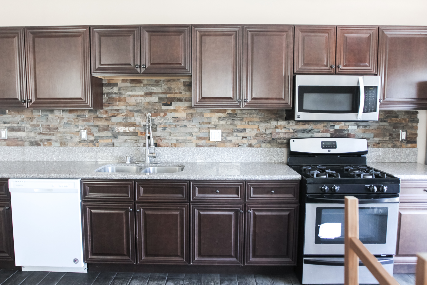 kitchen, dark wood cabinets, silver stove. silver microwave
