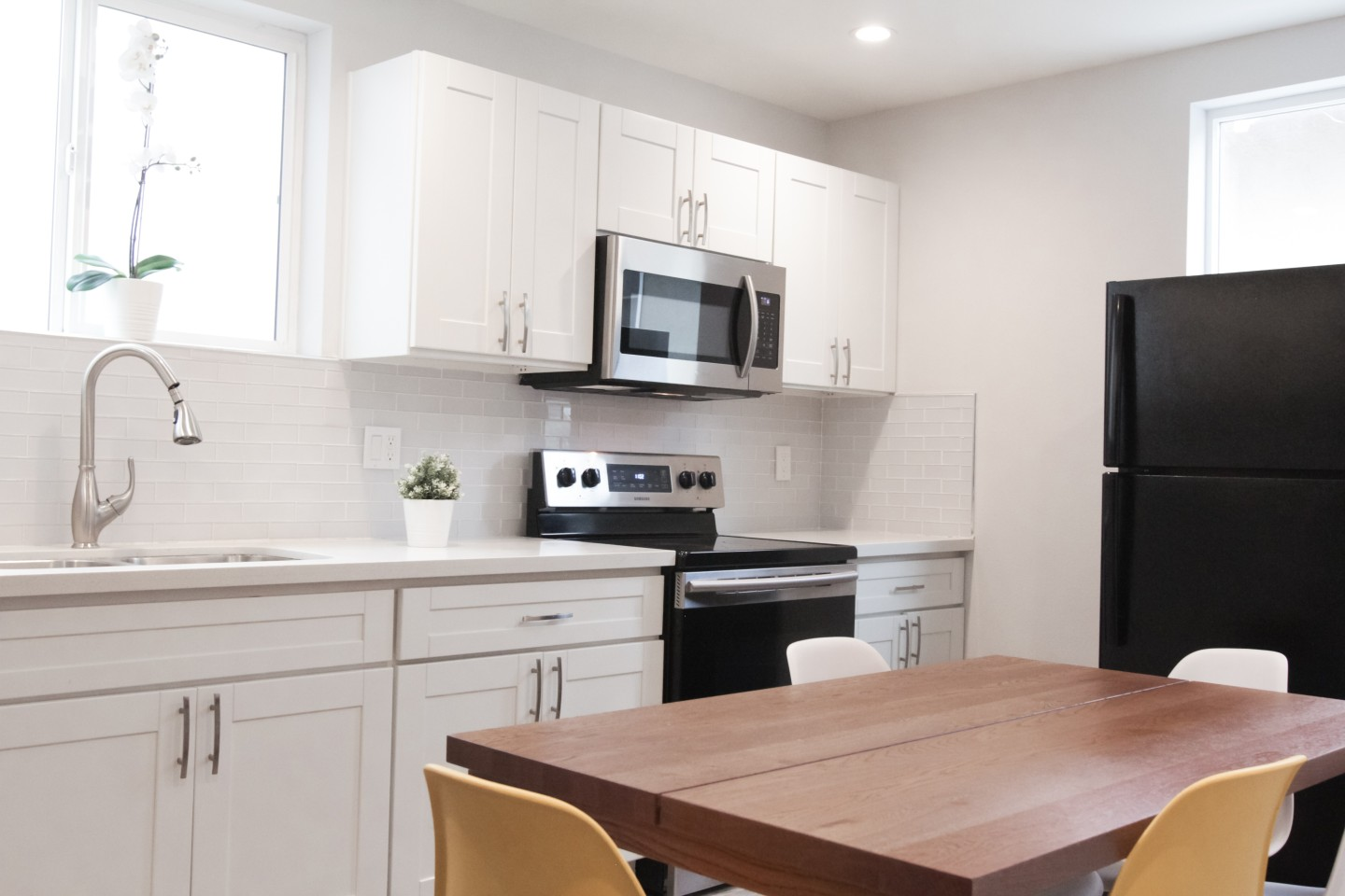 White kitchen with brown dining table