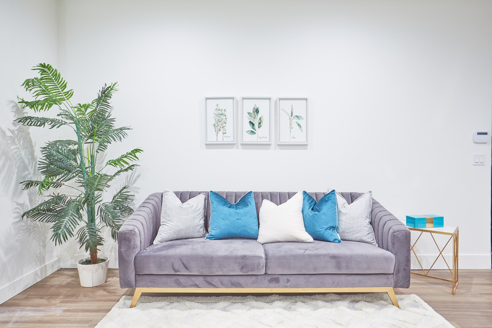 Tripalink model living room with grey and gold couch with green large plant