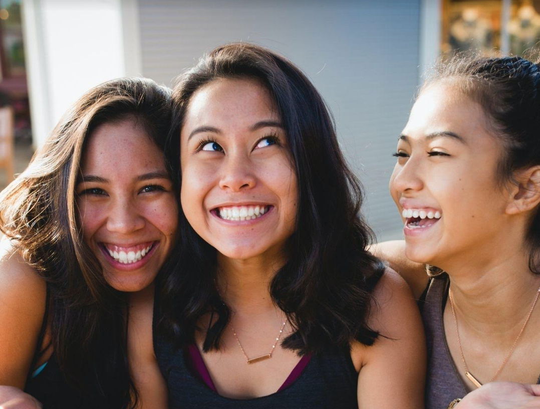 three female roommates laughing with each other