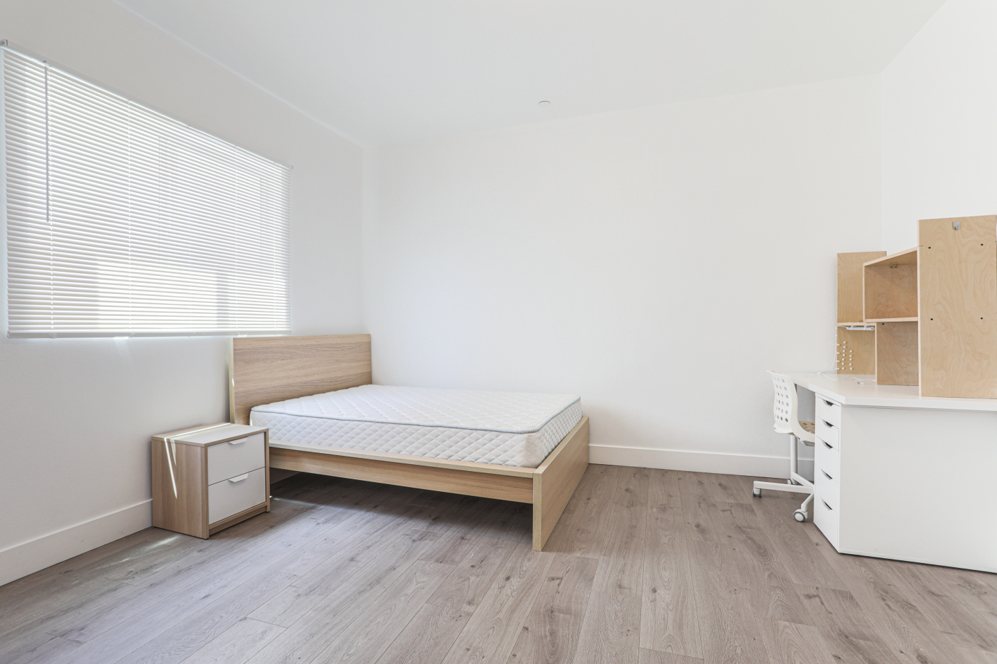 large bedroom with bed and hardwood flooring