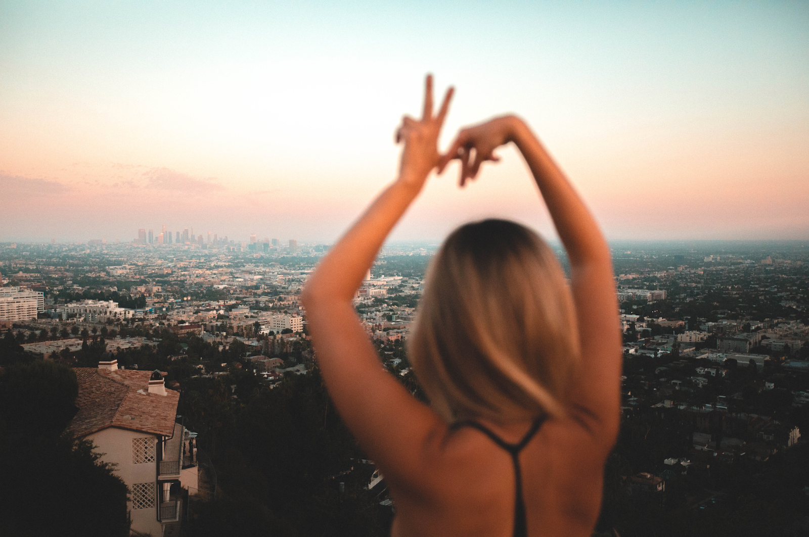 woman holding up LA finger sign and staring at the city