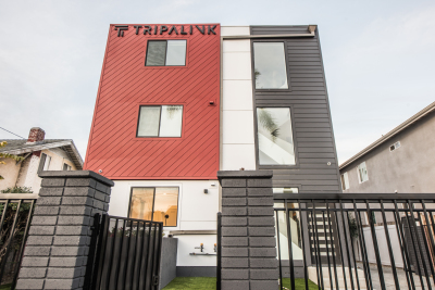 Red and grey exterior of apartment building, black gate,  Tripalink
