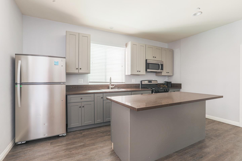 Apartment interior with silver refrigerator, Granite Kitchen Isle