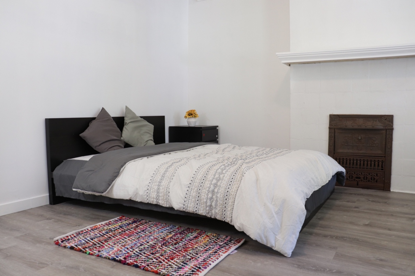 clean room, small bed with black bed frame, side view