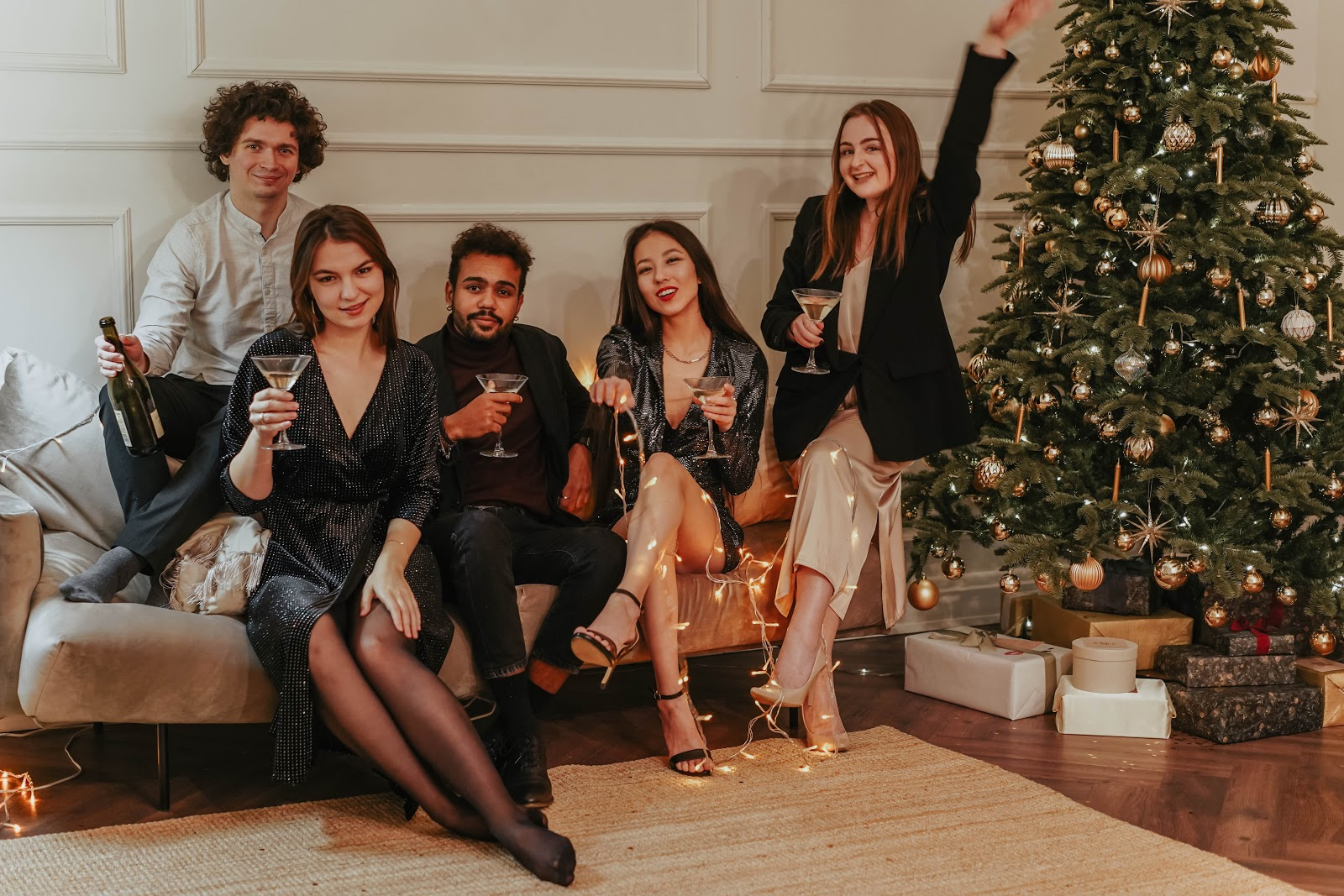 five people drinking wine and celebrating next to a Christmas tree