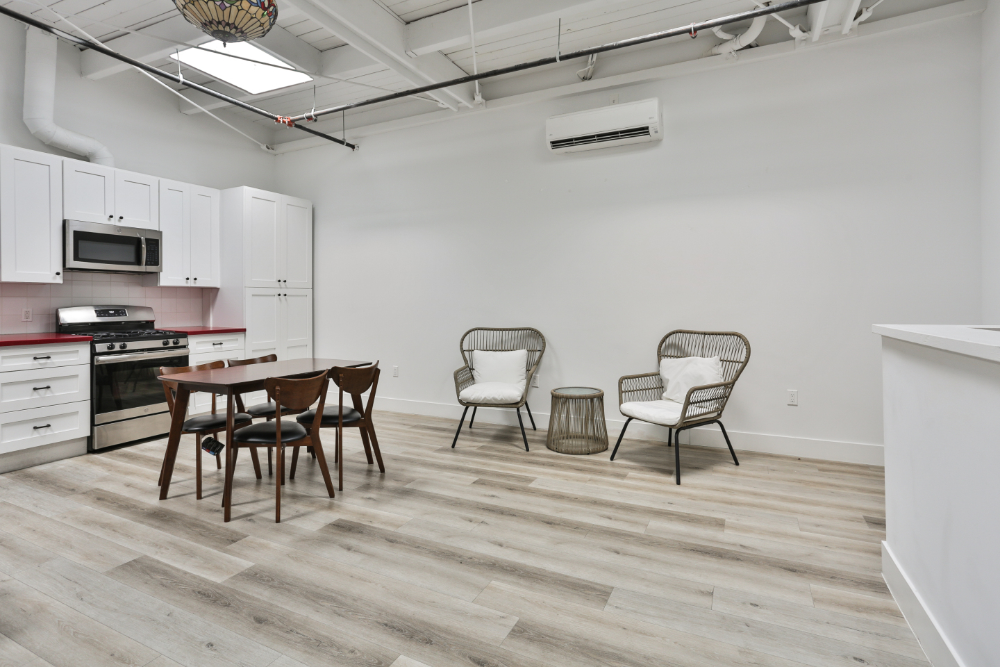 two lounge chairs and small table, large white kitchen