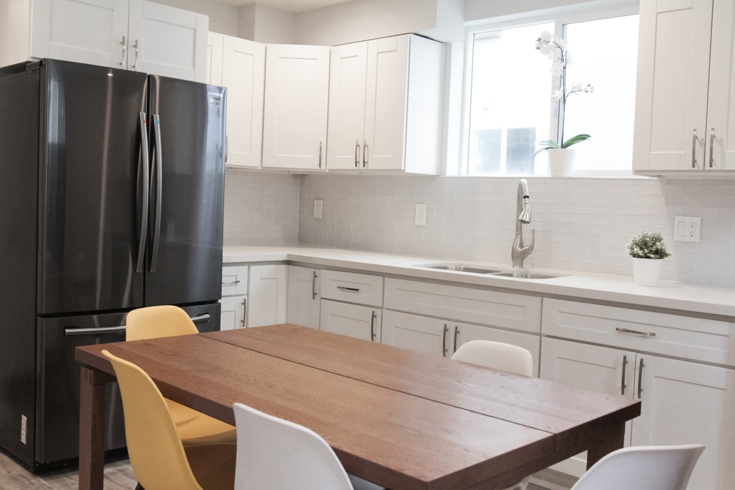kitchen with brown table and black fridge