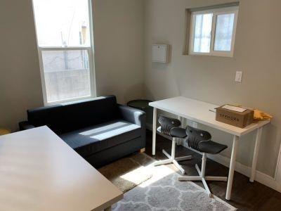 bedroom with dark couch, brown wood computer desk