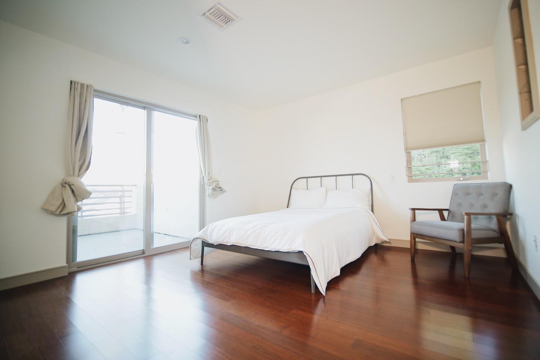 bedroom with white bed, brown hardwood floors