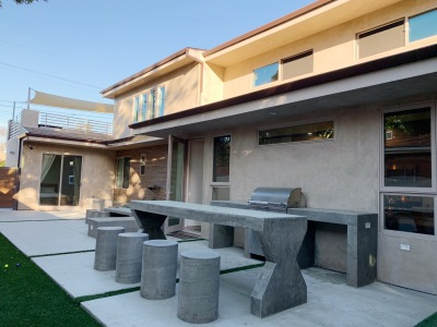 exterior of house with black chairs and black grill
