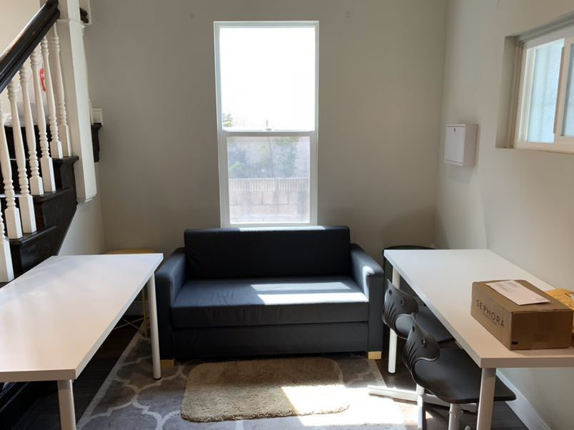 room next with dark staircase, white computer desk and small black couch