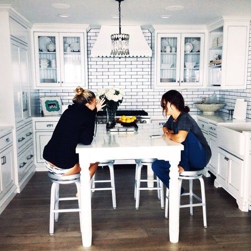 two women sharing living spaces in kitchen