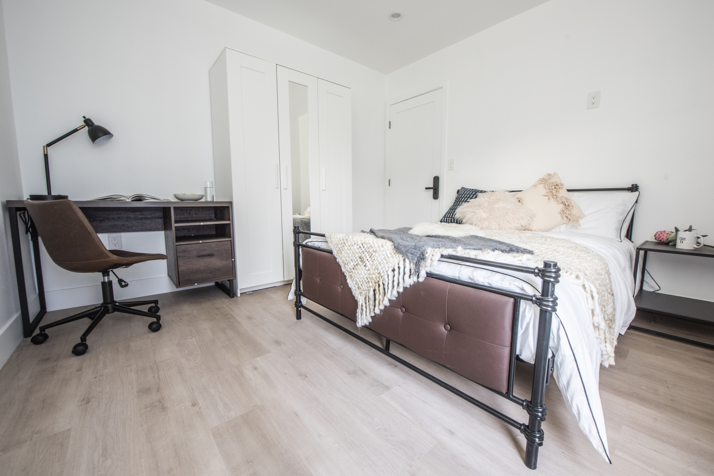 large bedroom with light brown hardwood floors and bed