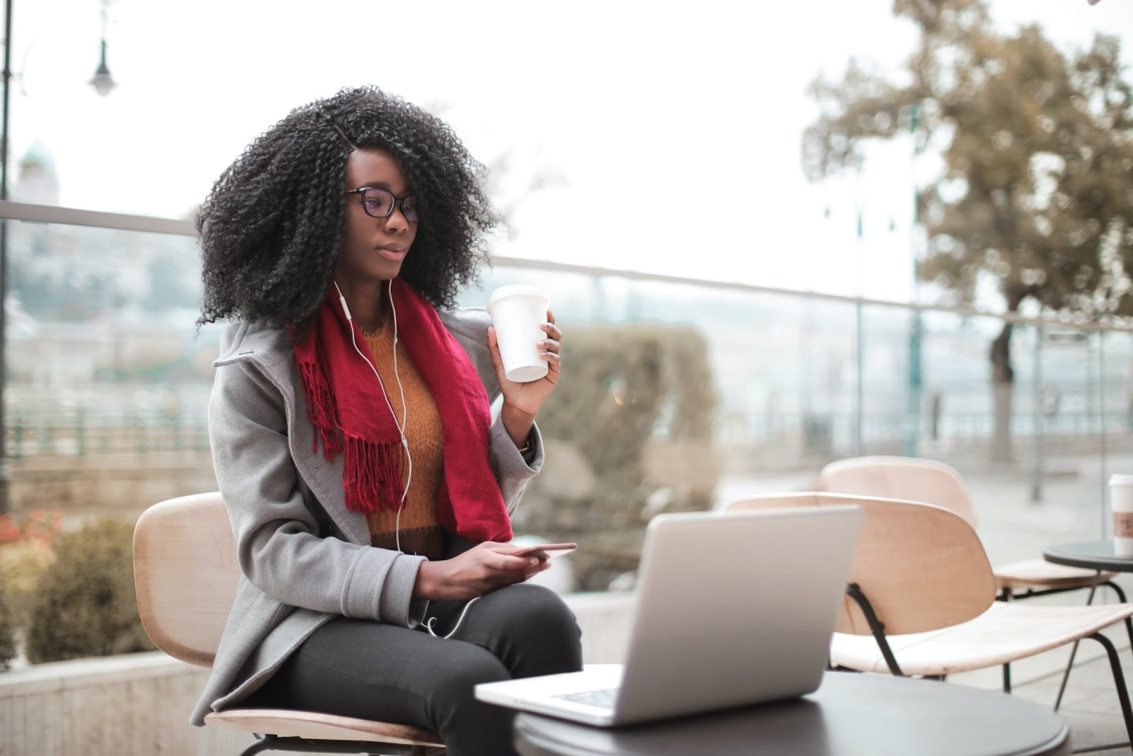Woman on grey laptop with curly hair