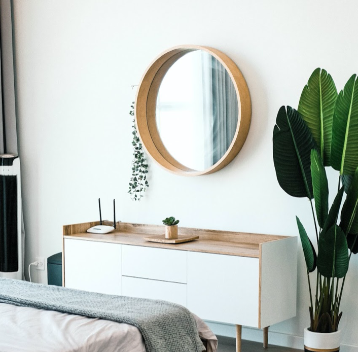 very clean modern apartment with circle mirror on the wall