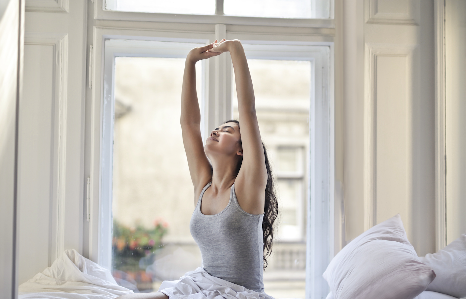 Woman waking up in Tripalink bedroom and streching