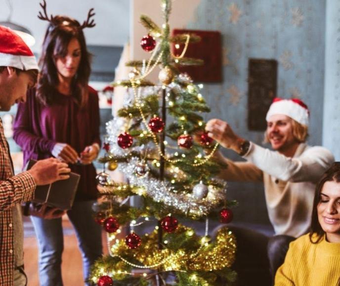 Three people decorating small tree