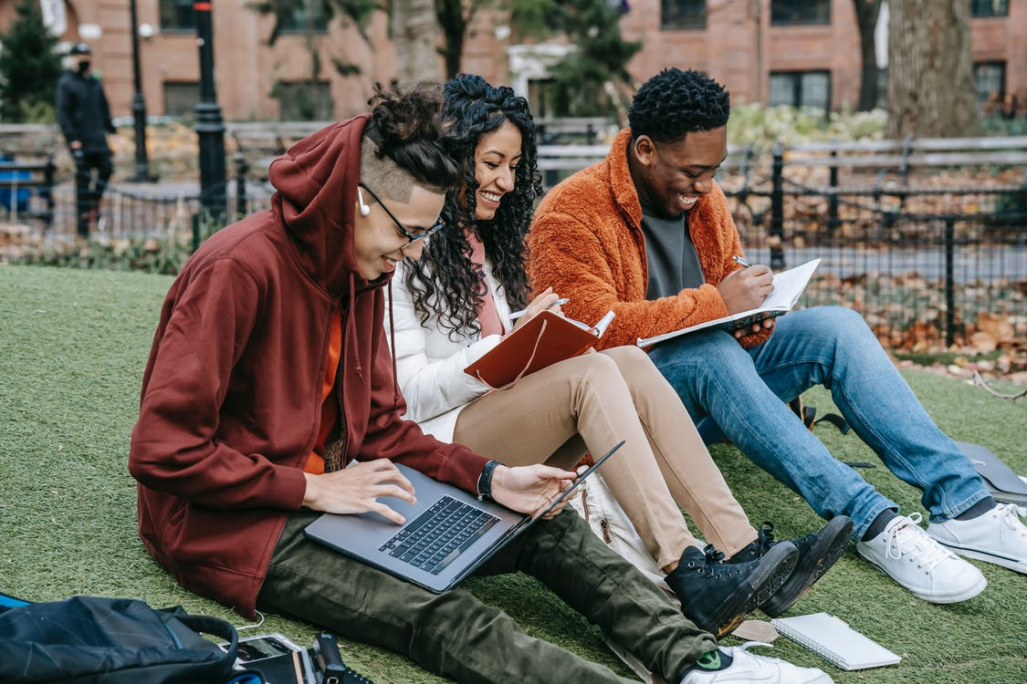 Happy multiracial group of graduate students in casual clothes sitting together on grass and studying with laptop and books