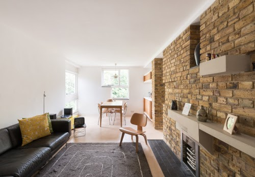 living room with stacked brick wall and black couch
