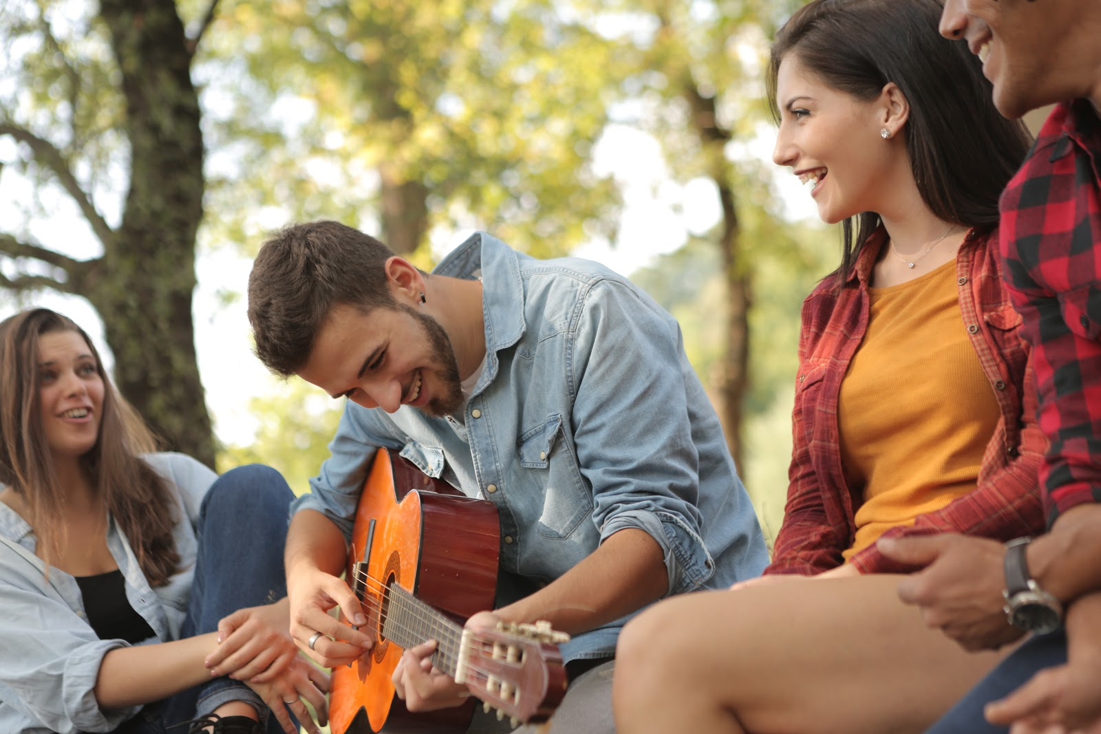 guy playing guitar with two women on his side