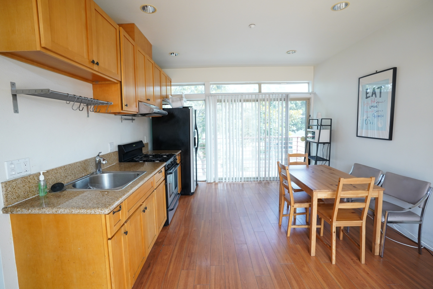 side view of kitchen, brown hardwood floors, brown cabinets and brown dining table