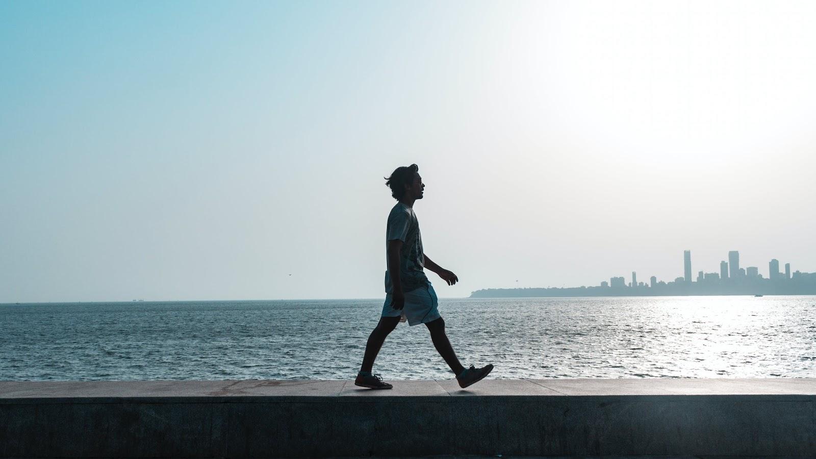 Guys silhouette walking next to water
