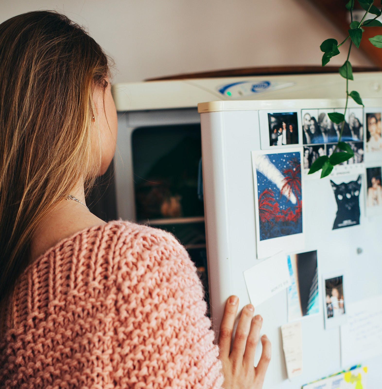 a woman looking in the fridge
