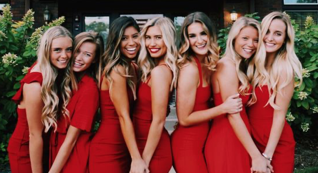 7 women in red dresses with long hair