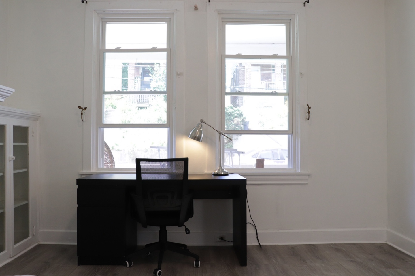 two windows, bright and clear, black computer desk with black lamp