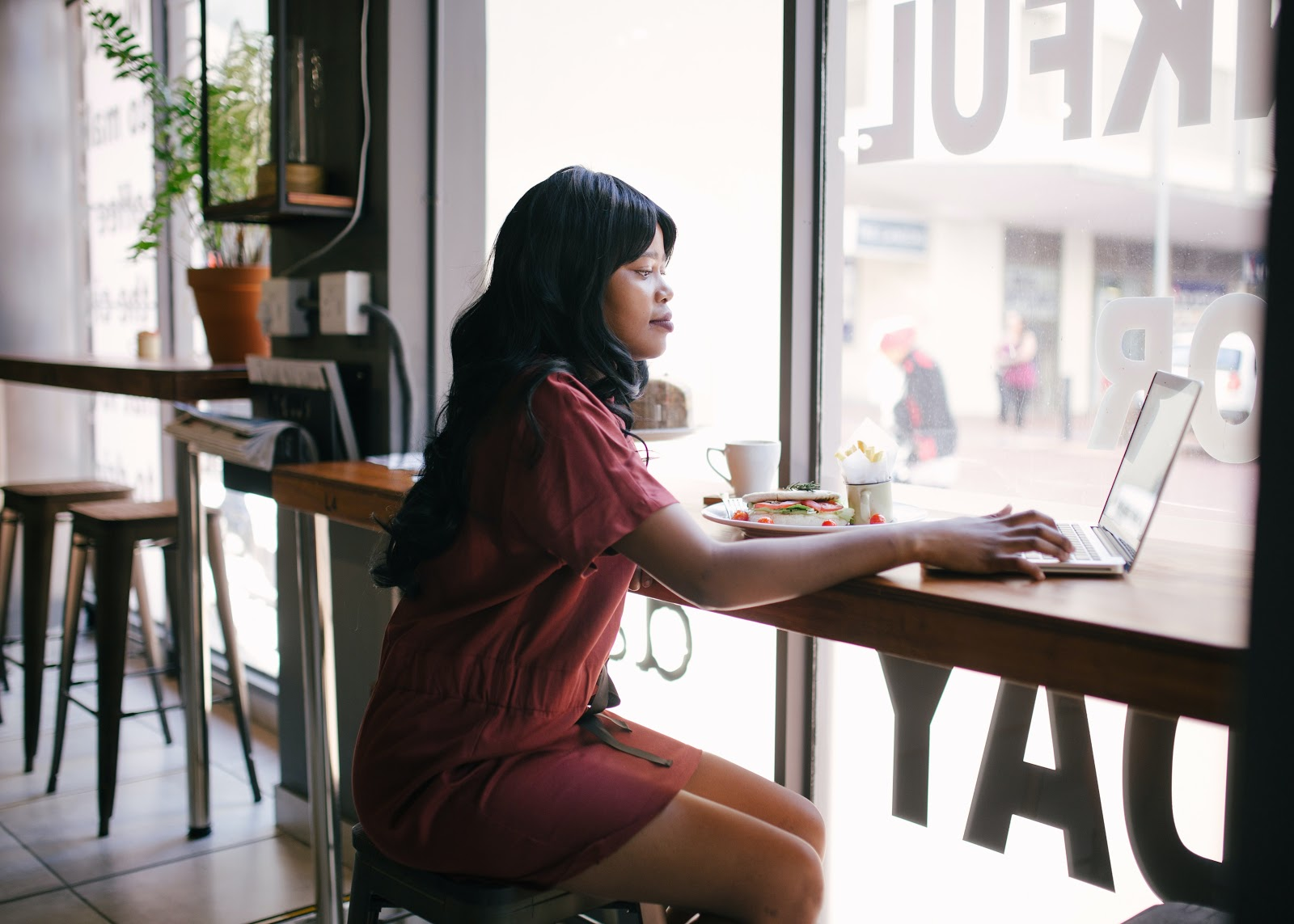 woman sitting on laptop in a cafe