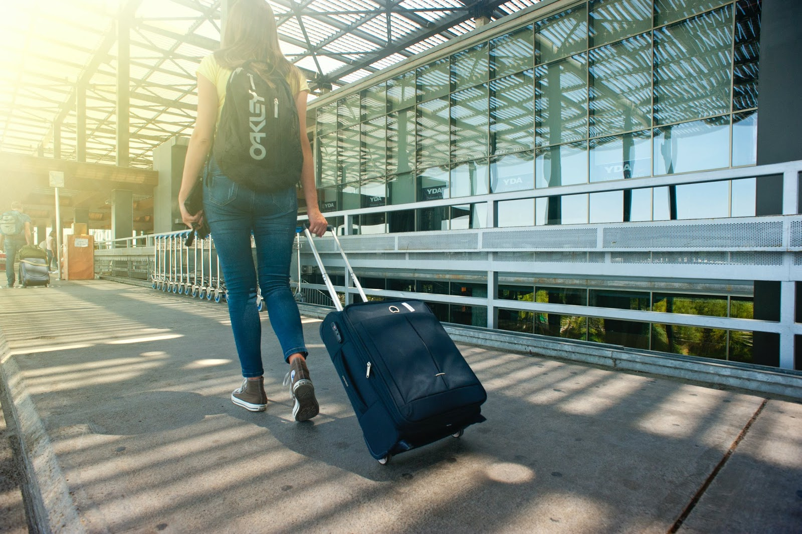 woman walking with rolling luggage and backpack