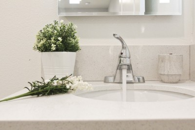 White sink with running water, green plant next to sink