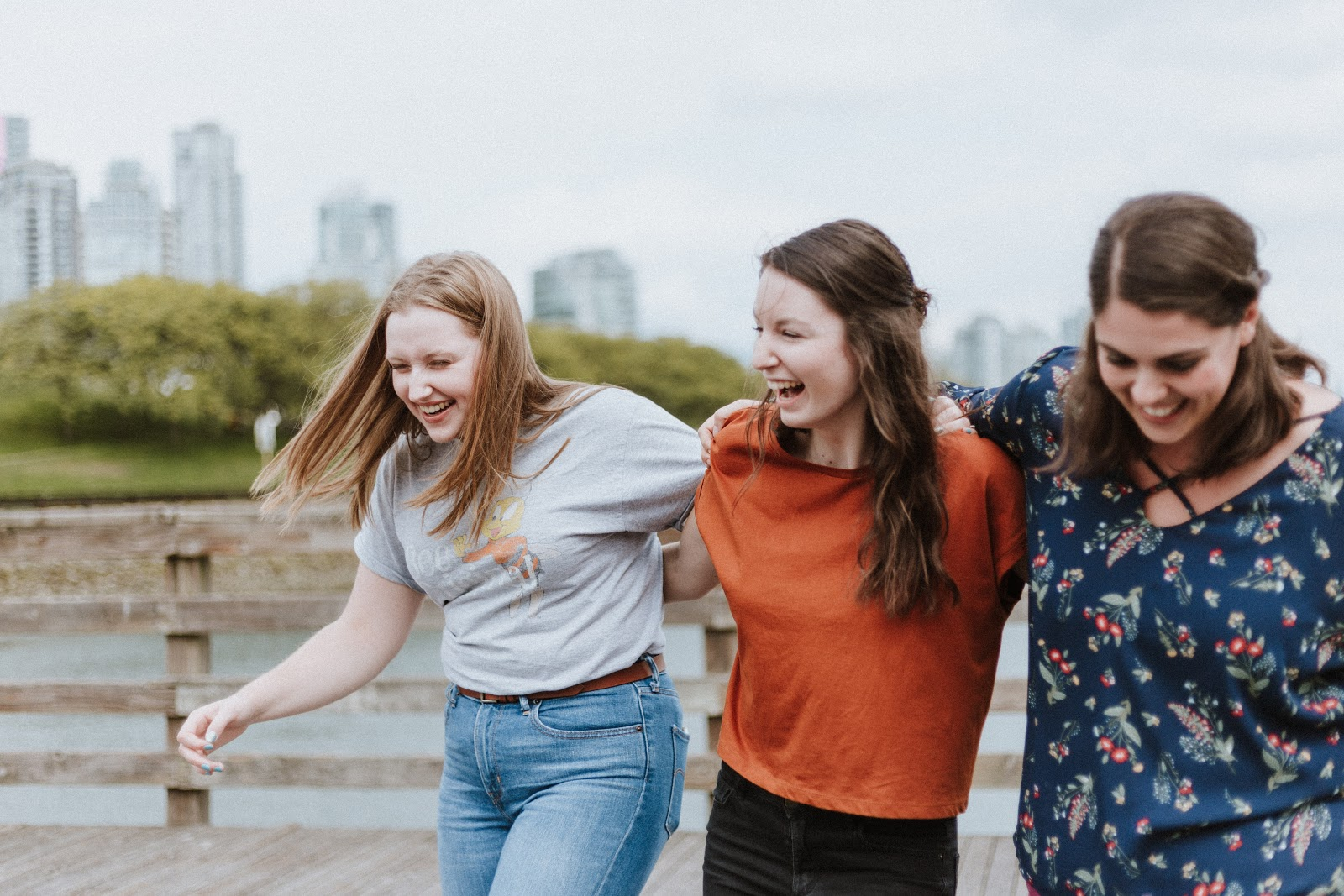 3 girls laughing and walking on pier
