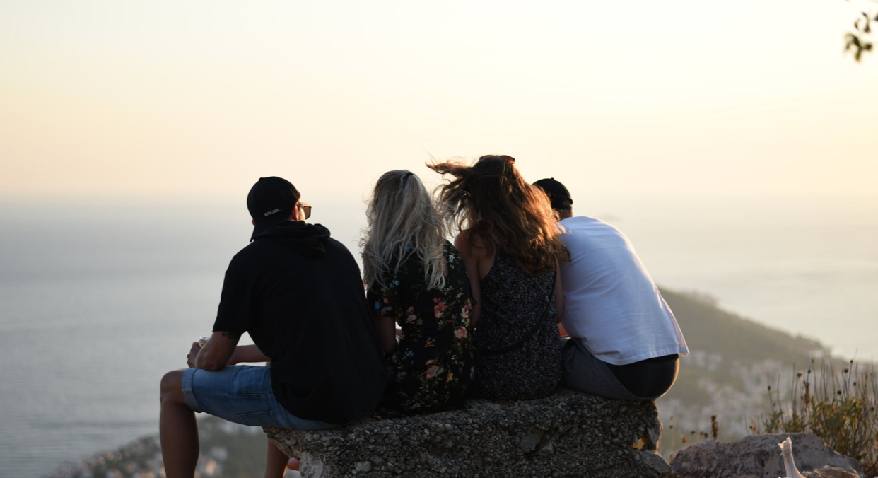 four people staring off into the coast