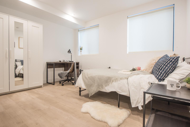 huge bedroom, light brown hardwood floors dark brown wood bed