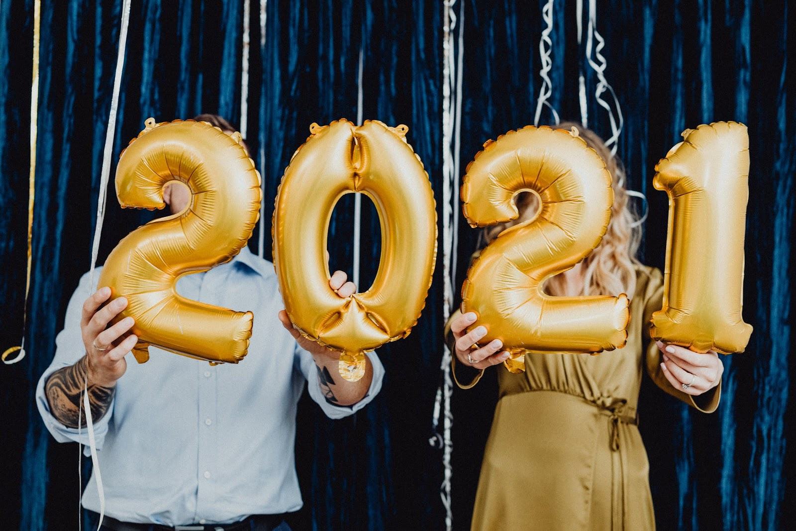 2 people hold 2021 balloons