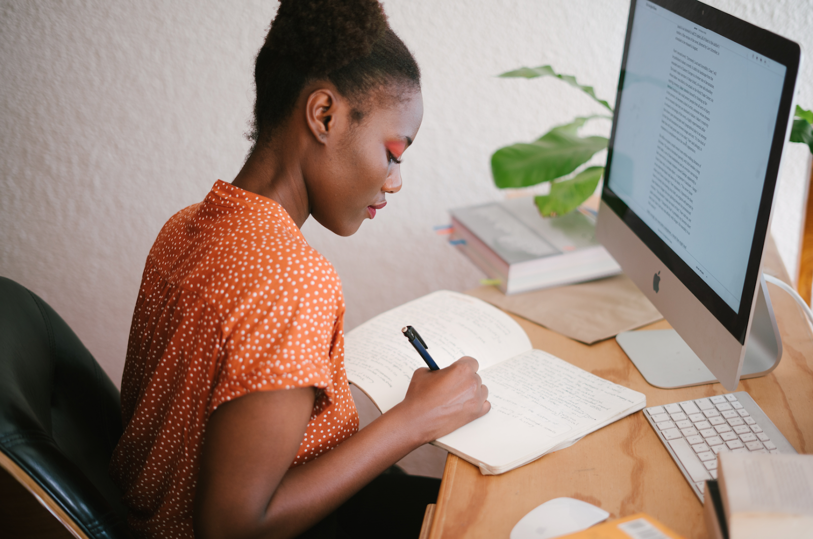 Girl writing in notebook in front of iMac