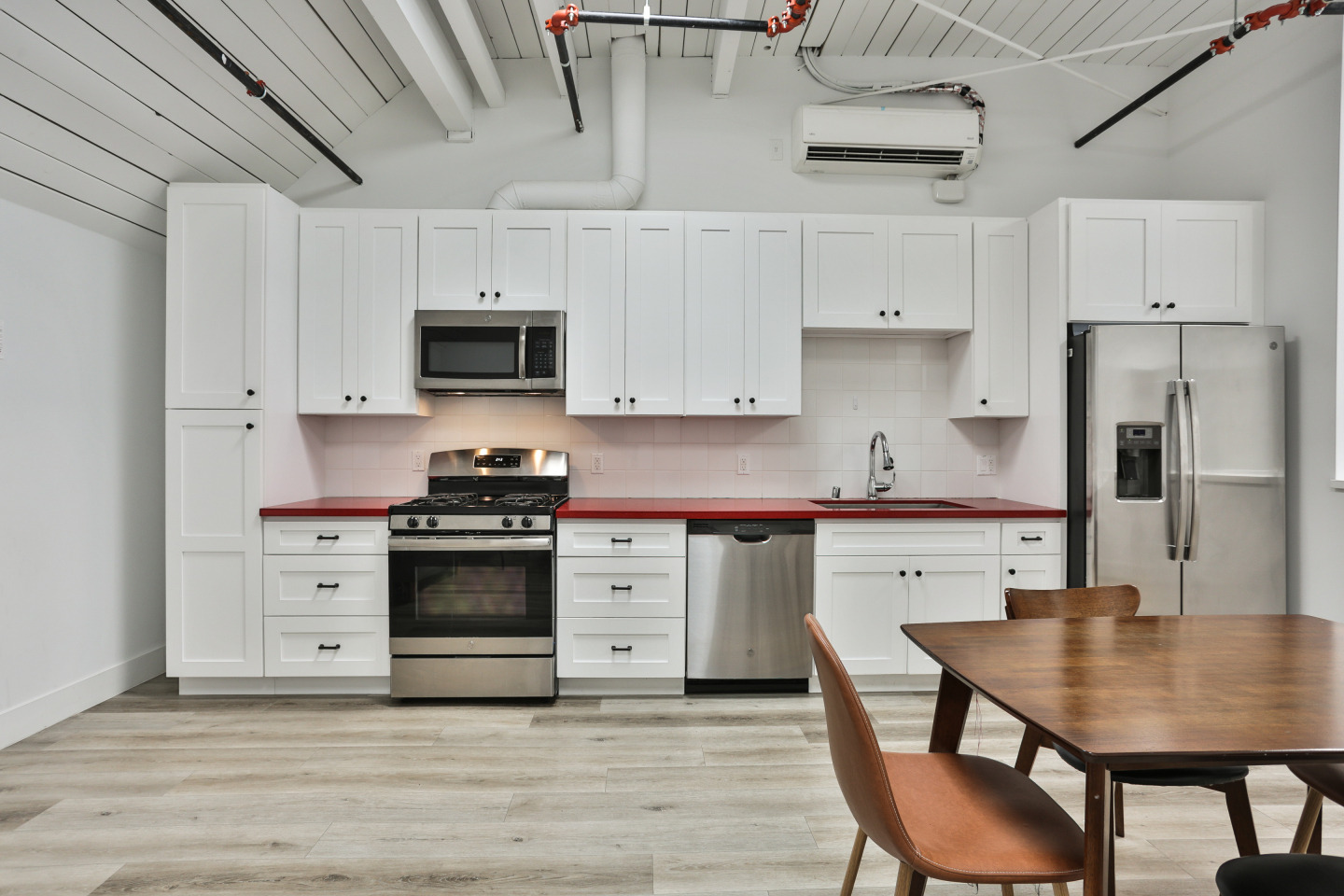 white kitchen, brown dining table, silver appliances
