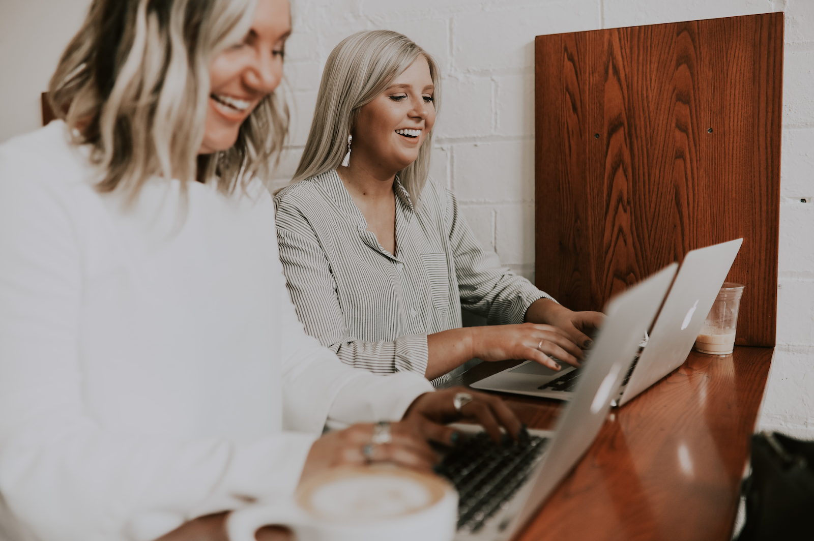 two blonde coworkers laughing with each other and typing