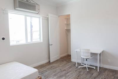 white one bedroom room, white desk with white rolling chair, Light brown hardwood floors