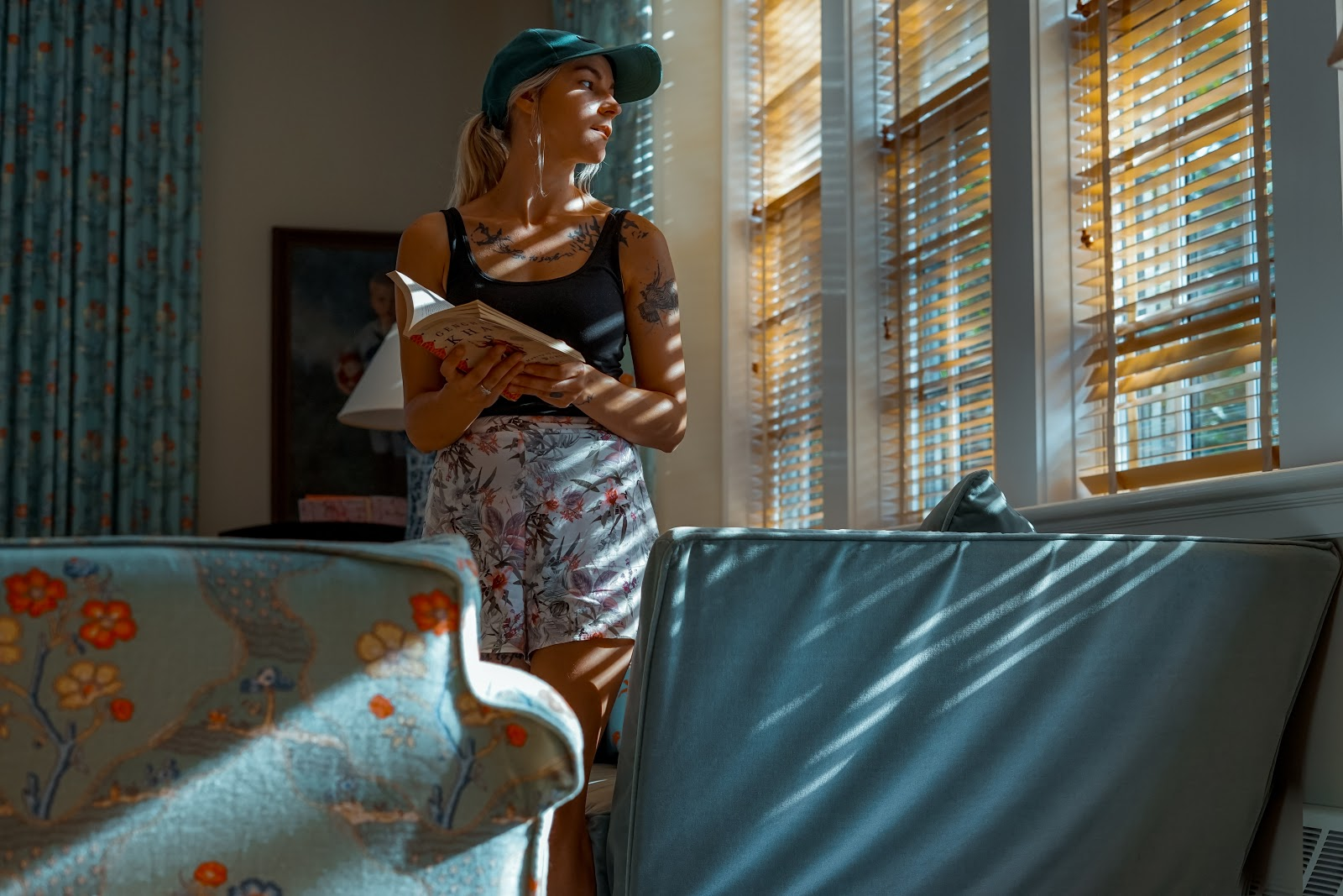 woman staring out window with blinds silhouette on her