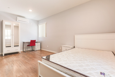 bright bedroom with bed, table and red chair