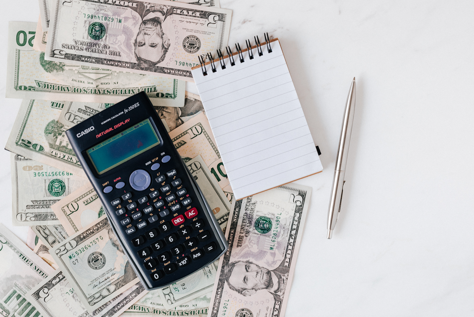 a calculator and memo pad sitting on top of spread out money