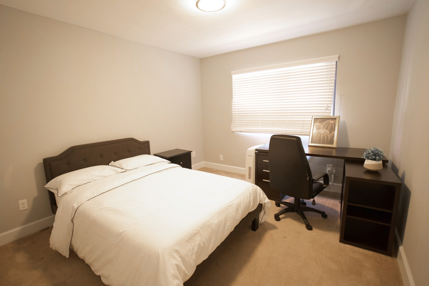 private bedroom furnished with black desk, chair and bed