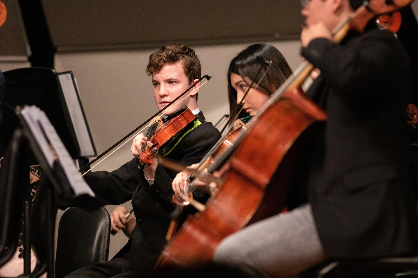 students in orchestra playing violins