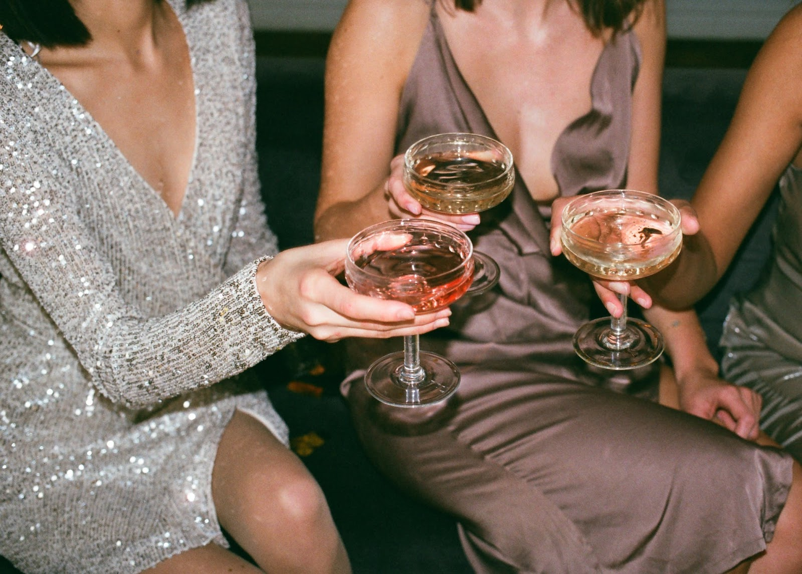 3 women giving wine toast in elegant gowns