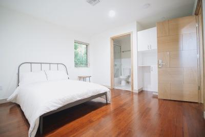 bedroom, white bed, steel bed frame, brown hardwood floor
